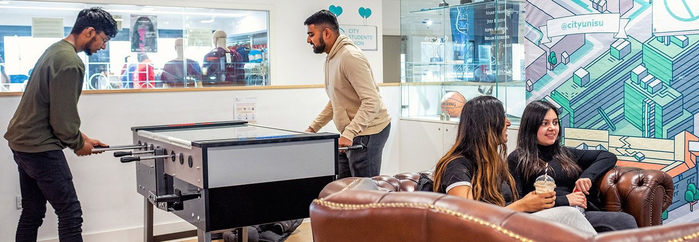 Students sitting and playing foosball in the student union