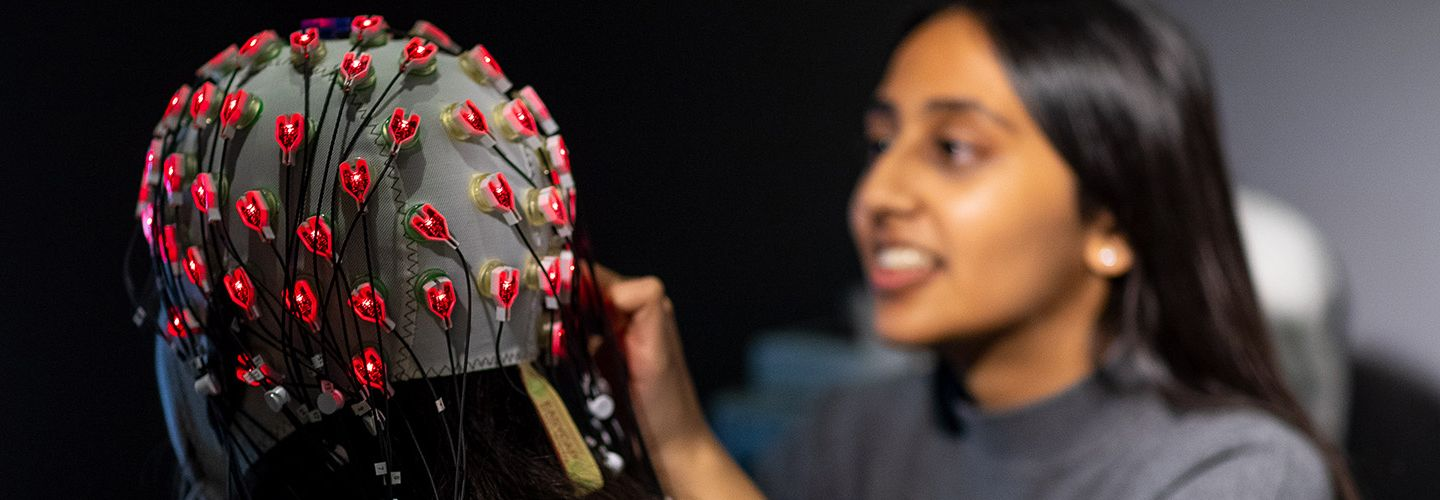 Female student putting electrodes on a patient's head