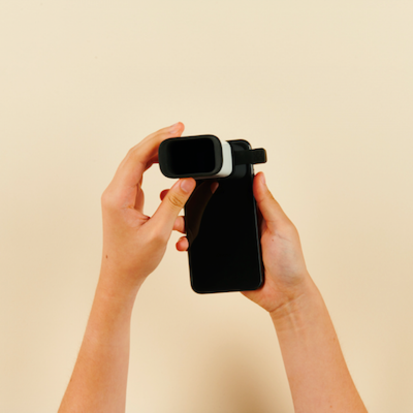 Hands holding a mobile and lens