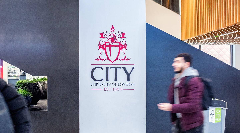 Male student walking past City logo