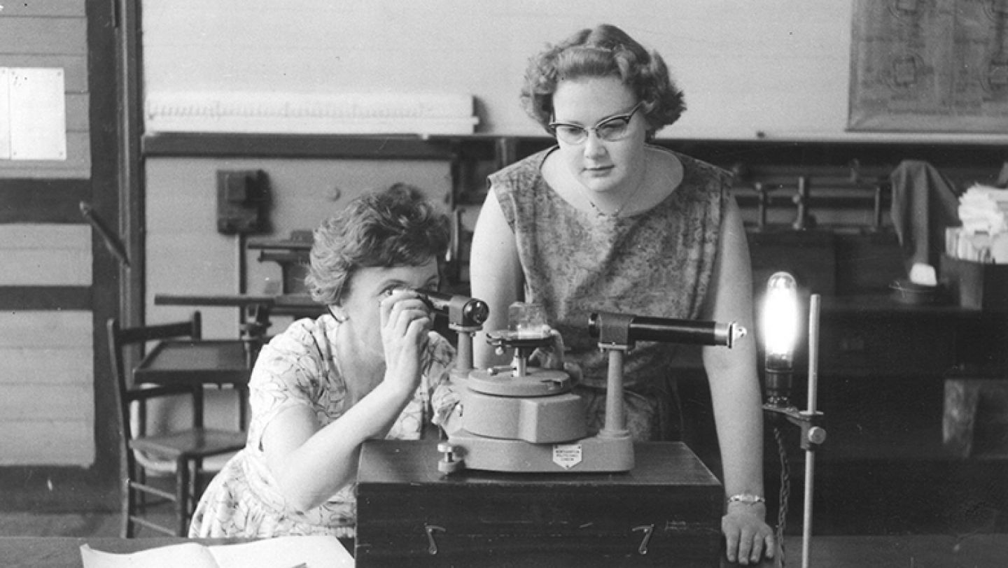 Two women using lab equipment in the Ophthalmic Optics Department, c.1960.