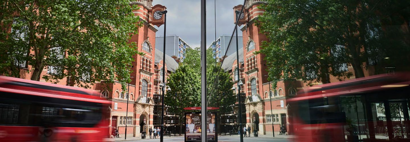 Rhind building with reflection of College building, buses and people.