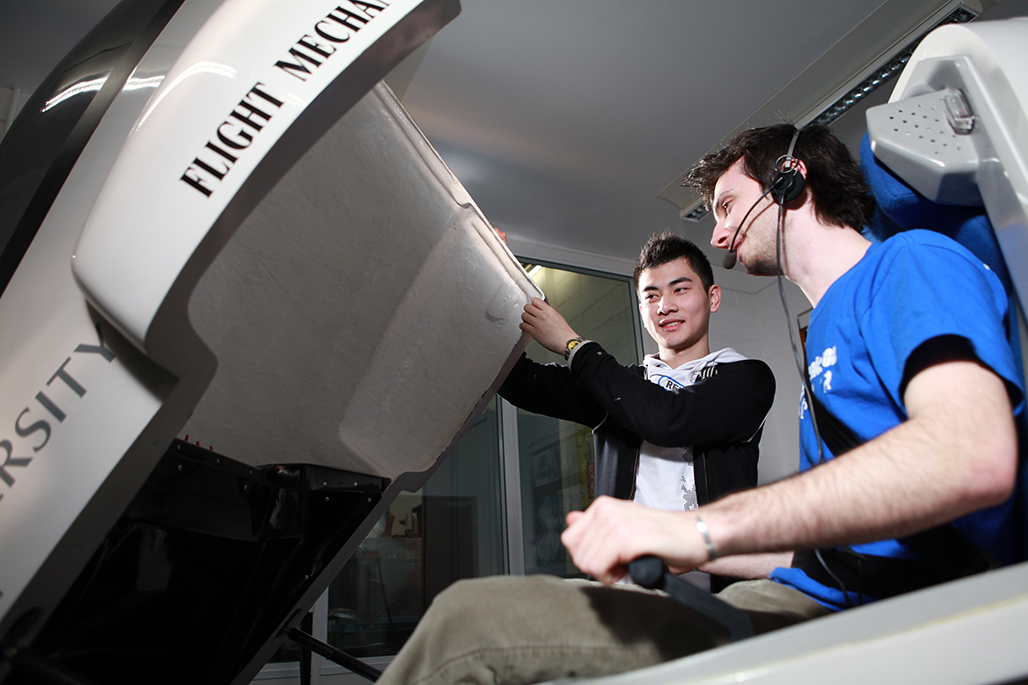 Male student in flight simulator as other student holds it open