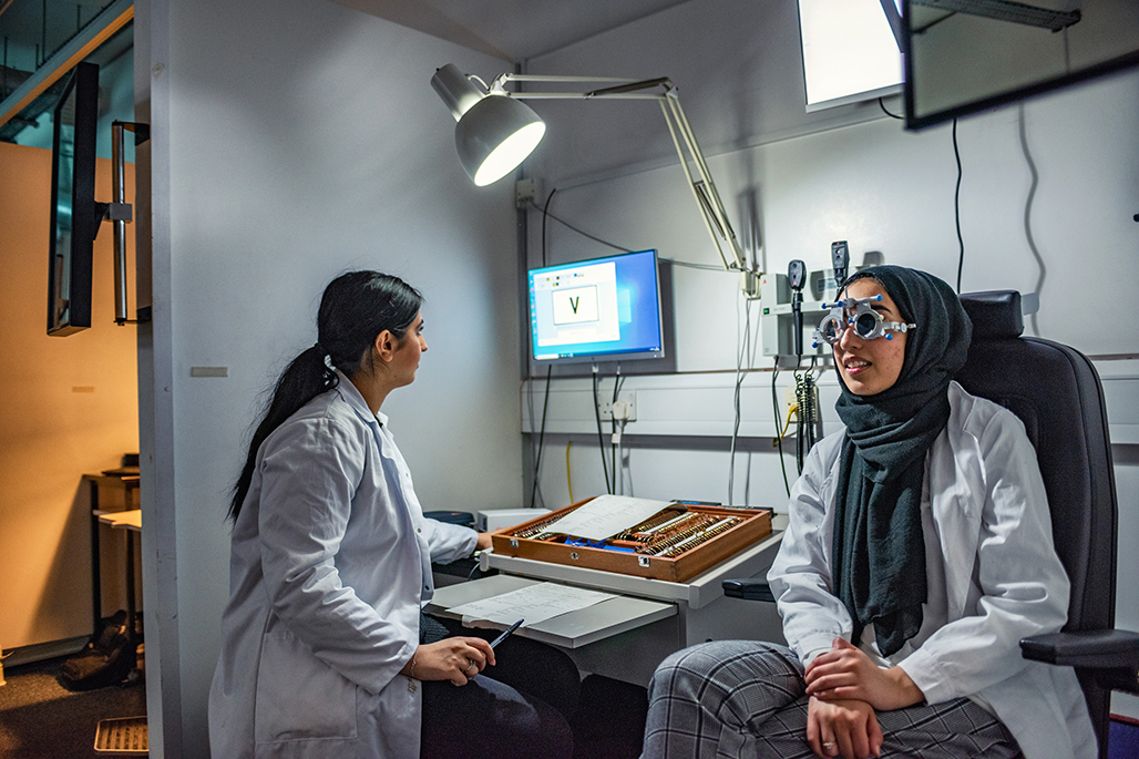 Optometry student conducting an eye examination