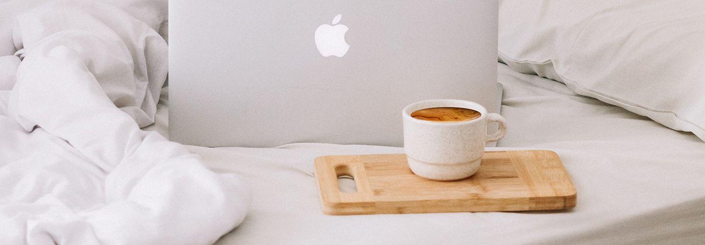 MacBook beside teacup with latte