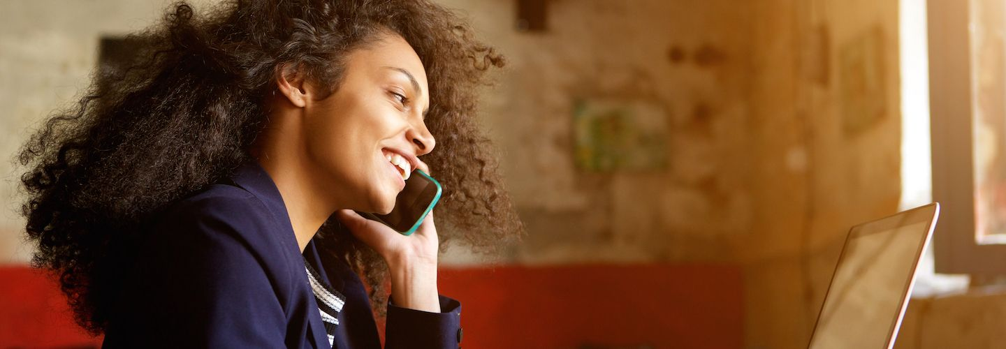 Closeup portrait of young woman relaxing with her laptop and making phone call