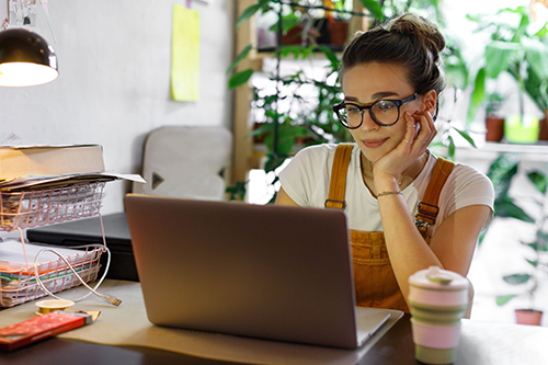 Woman working from home looking at a laptop screen
