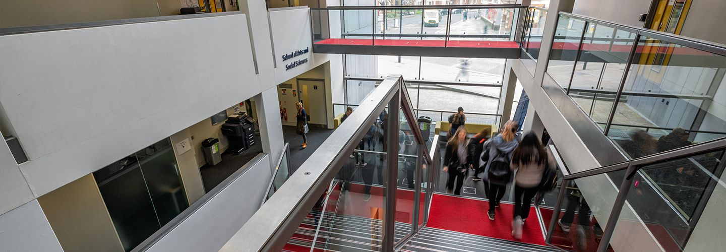 Students walking down the main stairscase in school of arts and social sciences