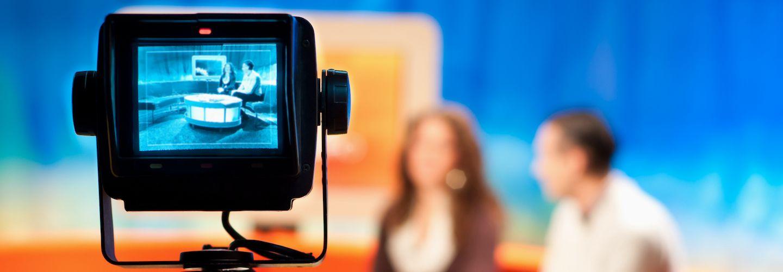 A camera recording a female and a male in a TV studio