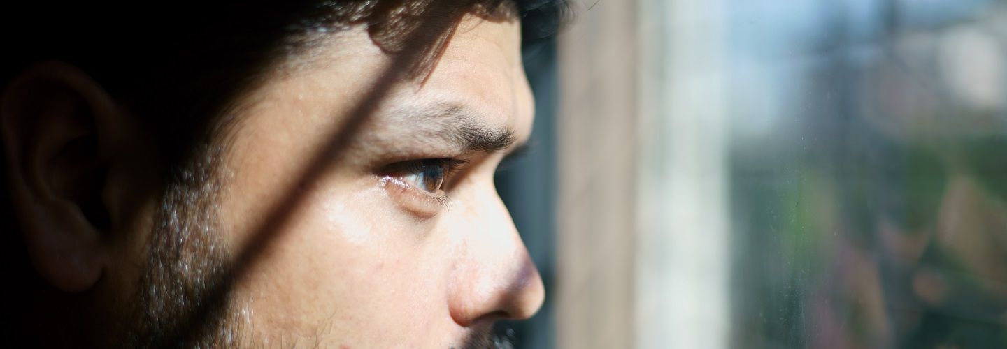 Man looking out of a window, face near glass.