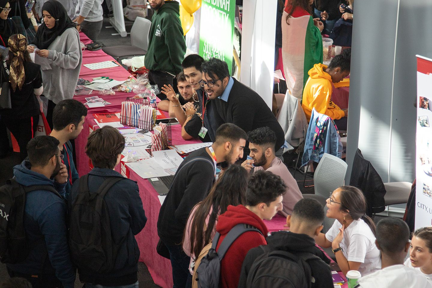 new students speaking face to face to clubs and societies member's at freshers fair