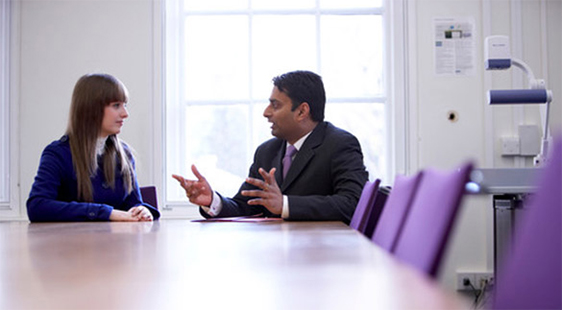 A female student and a male academic talking in a seminar room at City