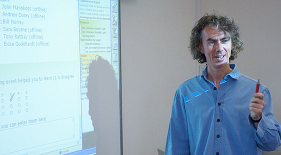 Image of a lecturer in front of a projector screen