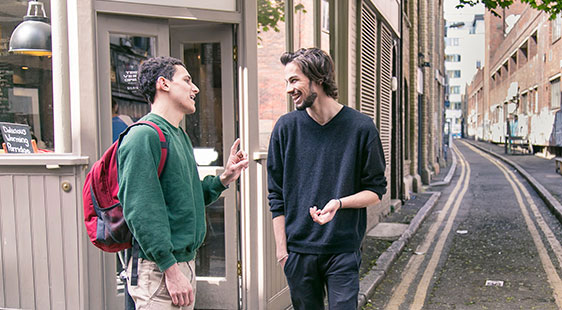 Two male students talking in the street in Clerkenwell