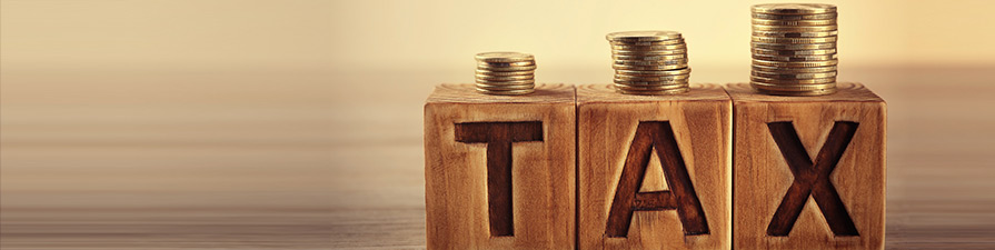 Tax concept with wooden blocks and coins on table