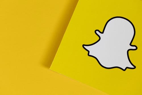 Snapchat logo on yellow paper.
