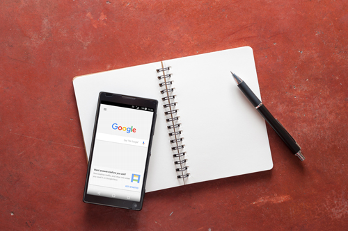 'Ok Google' app showing on android phone sitting on blank notebook. Google News Lab fellowship