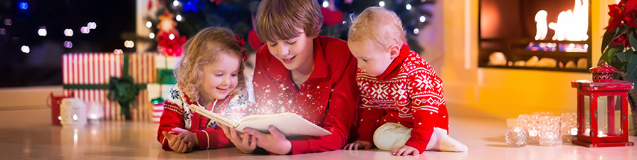 Three children reading at Christmas time