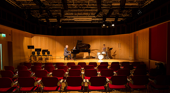 Pianist and drummer in College Building Performance Space