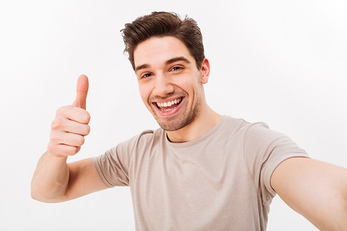 An image of a man taking a selfie on a blank, beige background.