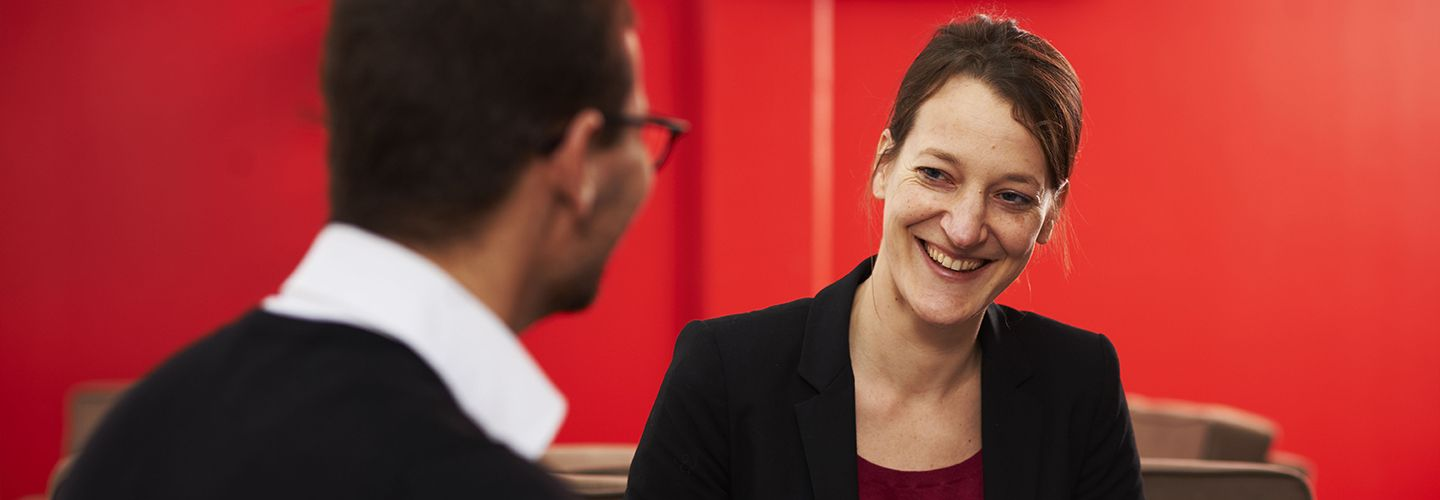 Dr Grietje Baars smiling at a colleague