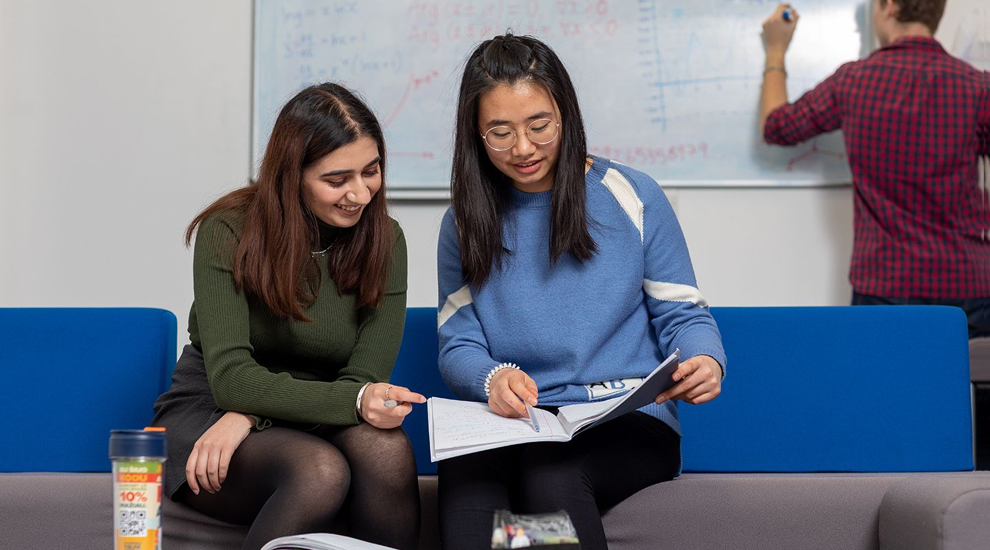 Two female students looking at a notepad