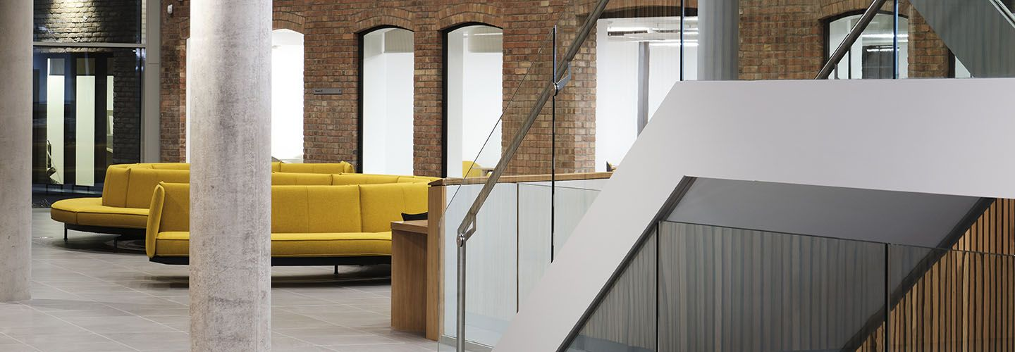 Internal of the Law School Building at ground floor level looking at stairs, yellow sofas and archways