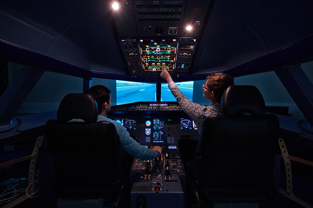 Two students inside a Airbus A320 flight simulator touching upper overhead panel