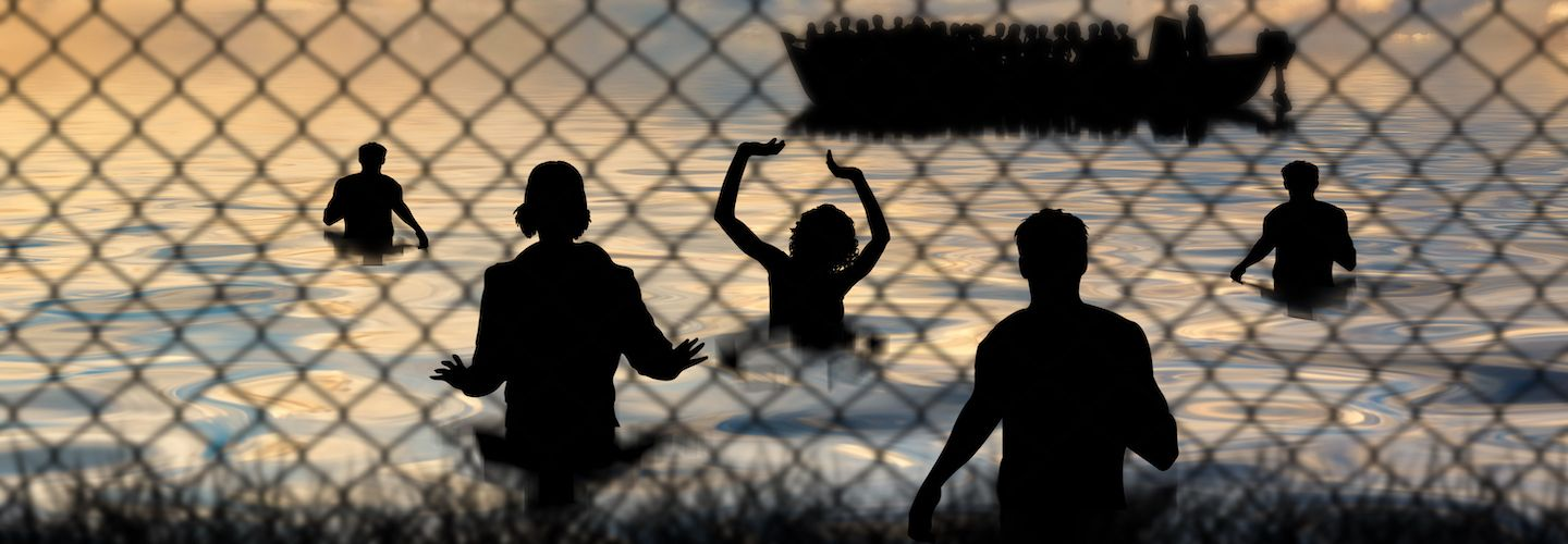 Refugees swim to shore against the backdrop of a chain wire fence