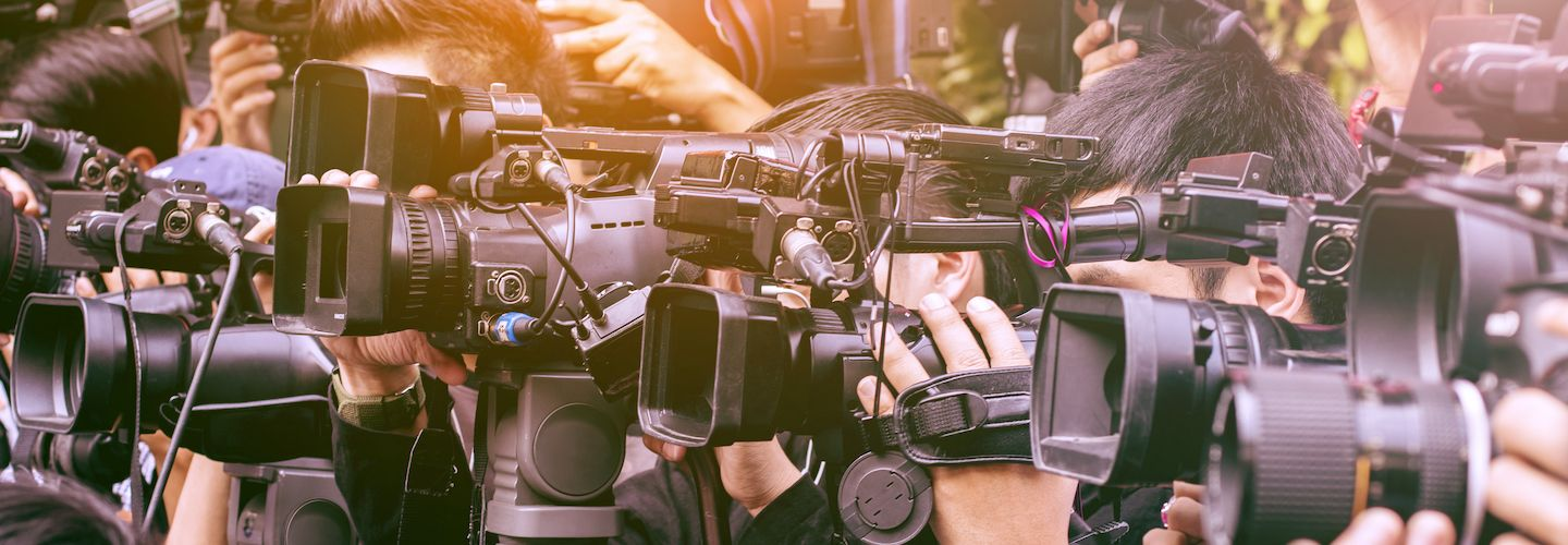 A large number of press and media reporters with their cameras at a broadcasting event