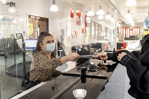 Receptionist in a facemask greeting a customer from behind a protective screen at the CitySight reception desk.