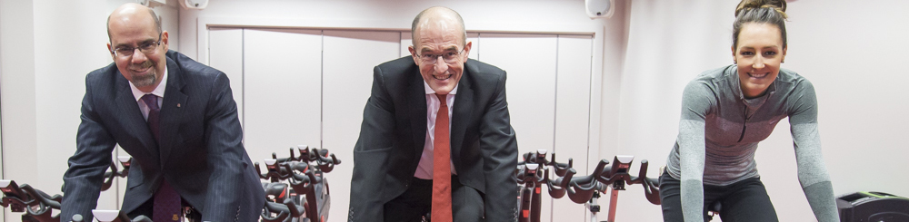 Vice Chancellor Paul Curran and others try out the stationary bikes at the CitySport Opening