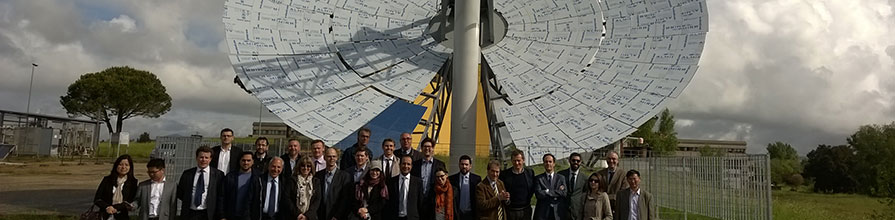 A group of people standing in front of a solar dish