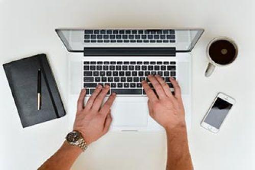 man writing on laptop