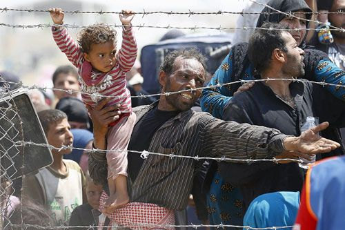 Refugee man and his young child look upset and angered in a crowd behind barbed wire