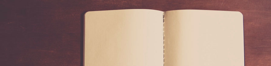 Unlined notebook open on a wooden table