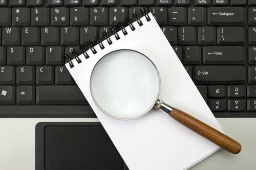 Magnifying glass and notepad on a laptop keyboard