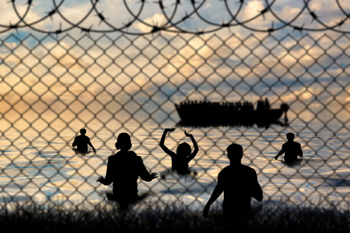 Refugees swim to shore against the backdrop of barbed wire fence