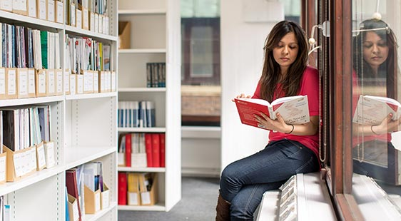 A female student reading a book in a university library at City