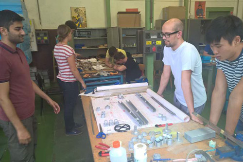 Students looking at the metal tubes and joining pieces laid out on their work bench.