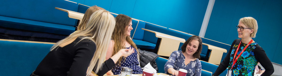 Students speaking with academic in lecture theatre