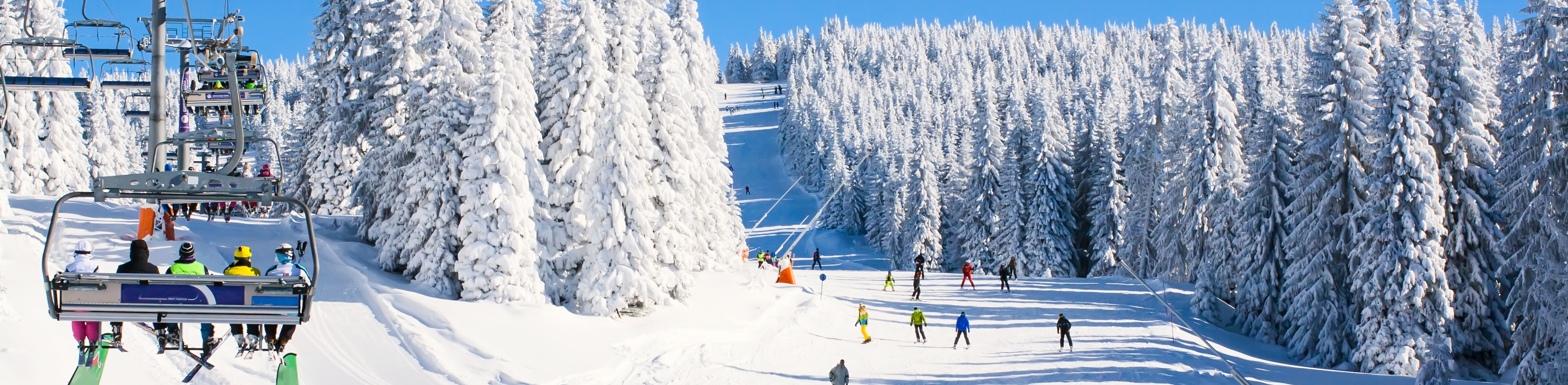 people ski down a slope with a chair lift carrying people up the mountain. Blue sky and snow-covered trees