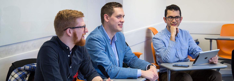 Three male postgraduate students listening