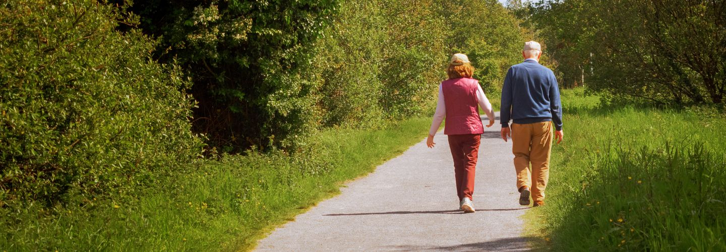 Old couple walking on a footpath on a warm sunny day.