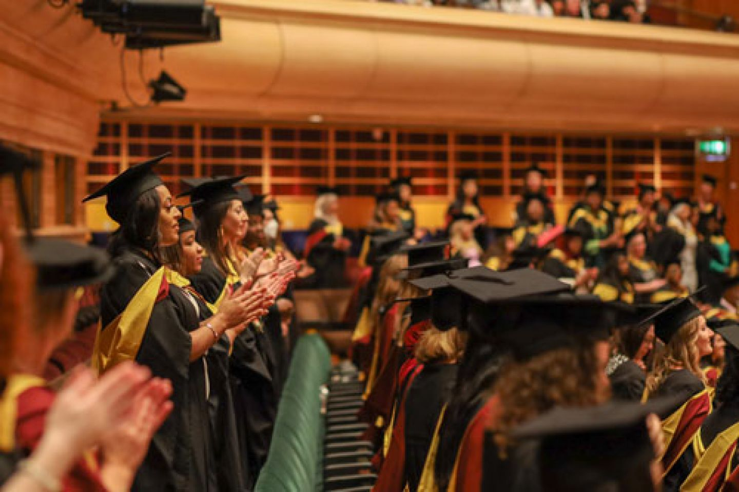 City graduates applaud each other in the auditorium at The Barbican Centre.