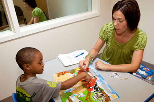 A speech therapist helps a child with Aphasia