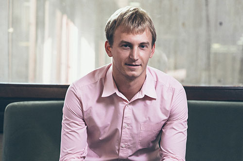 Joe Wilkinson wearing a light pink shirt and smiling
