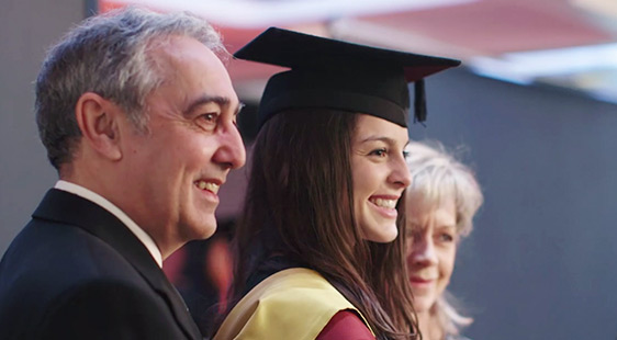 A female student in graduation dress with her parents