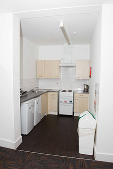 View of kitchen in a one bed flat. Double oven with electric hob and extractor fan, sink and draning board, fridge and 5 draws and cupboards