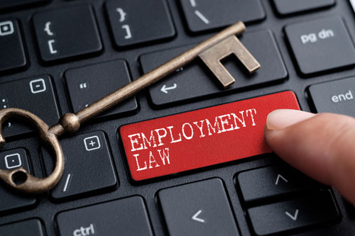 Closed up finger on keyboard with word 'employment law'
